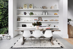 Designer chairs and a rustic wooden table in front of a niche with shelves