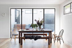 Dining table with benches and chairs in front of a patio door in an open living room