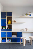 Shelf system with blue fronts and integrated table top in the boy's room