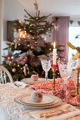 Christmas tree behind dining table set in classic style with sugar-coated apples on plates