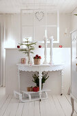 Christmas decorations on semicircular console table against partition