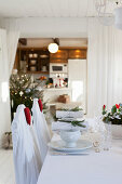 Table set for Christmas in rustic, white dining room