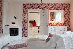 Blick vom Wohnzimmer mit Kamin und Blumentapete in die Küche