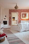 Wohnzimmer im skandinavischen Landhausstil mit Kamin und roter Tapete
