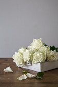 Bunch of white roses on white shabby-chic tray