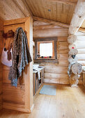 Coat rack on partition wall in rustic bathroom of log cabin