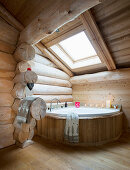Corner bathtub below skylight in log cabin