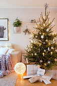 Decorated Christmas tree and gifts wrapped in white paper