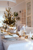 Table dramatically set for Christmas with conifer branches and fairy lights