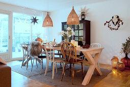 Verschiedene Stühle um weihnachtlich gedeckten Tisch