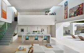 Moderner offener Wohnraum mit Galerie und offener Wand zum Pool