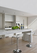 Barstools at angular marble table in minimalist kitchen