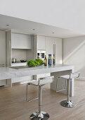 Barhocker vor eckigem Marmortisch in minimalistischer Küche