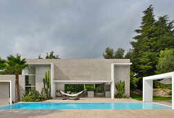 Modern architect-designed house with pool under cloudy sky