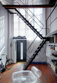 Metal staircase leading to gallery in high-ceilinged narrow room