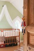 Hampelmann am Griff der Holztür zum nostalgischen Kinderzimmer