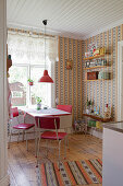 Red retro chairs around table in kitchen-dining room with vintage-style wallpaper
