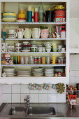 Retro crockery on kitchen shelves with lace trim above sink