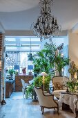 House plants and chandeliers in elegant lounge with antique ambiance
