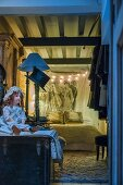 China doll, fairy lights and wall hanging in vintage bedroom