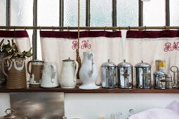 Arrangement of vintage objects on wall-mounted shelves against hand-made curtains embroidered with initials