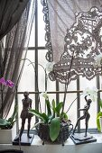 Two sculptures and orchid on windowsill below lace curtain