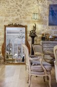 Gilt-framed mirror leaning against stone wall in elegant Belle Époque interior