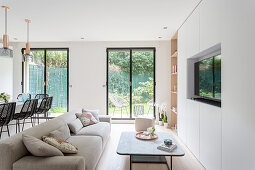 Fitted cupboards incorporating TV, coffee table and sofa in living room with floor-to-ceiling windows overlooking garden