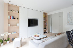 Modern fitted cabinet surrounding TV in white and beige living room