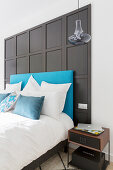 Bed with turquoise headboard against black panelled wall