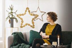 Frau sitzt auf Sofa vor DIY-Weihnachtssternen aus Naturmaterialien