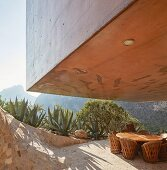 Concrete house projecting over round table on terrace with panoramic view