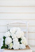 White hydrangeas on old chair against board wall