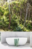 Modern outdoor bathtub with a view of the summer forest