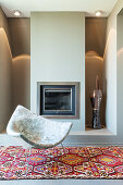 Designer armchair on patterned rug in front of fireplace