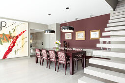 Upholstered chairs in elegant dining area with claret-red wall between huge artwork and cantilever staircase