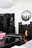 Elegantes, schwarz-weisses Wohnzimmer mit Kaminfeuer