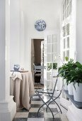 Helle Loggia mit rundem Tisch und geöffneten Fenstertüren
