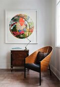 Classic armchair next to retro lamp on antique cabinet below modern colourful painting