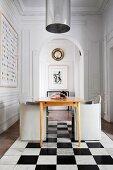 Tisch und Designerstühle im Zimmer mit Stuck und Marmorboden im Schachbrettmuster