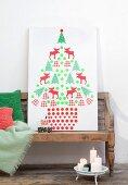 Stilisierter Weihnachtsbaum aus ausgeschnittenen Motiven auf weiße Platte geklebt