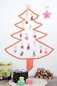 Weihnachtsbaum aus Masking-Tape auf weißer Wand und mit verschiedenen Anhängern