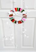Circular door wreath made from colourful satin ribbons with Merry Christmas motto