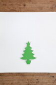 Christmas-tree silhouette cut out of green paper on white surface