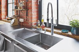 A stainless steel sink in front of a window and a brick wall