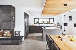 A minimal, open-plan kitchen with suspended reclaimed wood ceiling