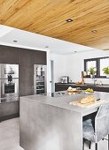 An anthracite-look island in front of a cupboard with built-in appliances and a suspended reclaimed wood ceiling