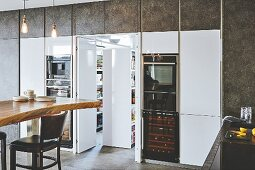 Küche mit weissen Hochglanzfronten und verstecktem Nebenraum