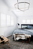 Double bed with linen blanket and coat rack with animal fur in the attic bedroom