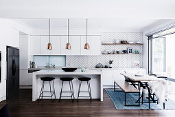Open kitchen with breakfast bar and cozy dining area in front of the patio door